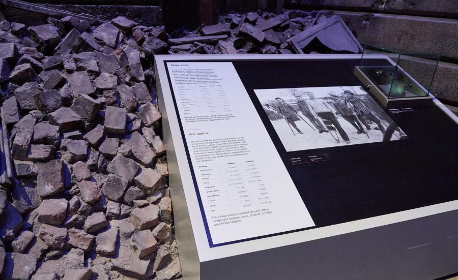 Tablica, na której podano liczbę ofiar II wojny światowej umieszczona w sali, w której odtworzono zniszczoną podczas wojny ulicę