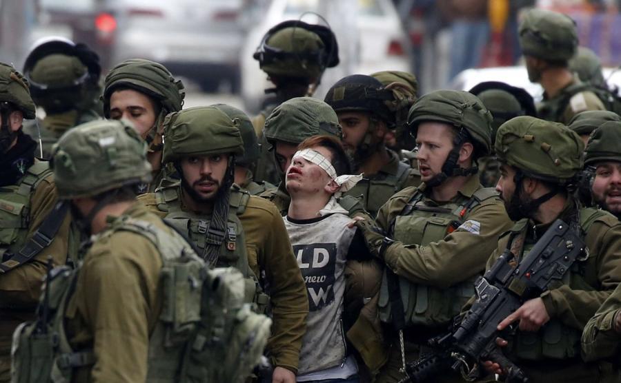 Izraelscy żołnierze i młody Palestyńczyk