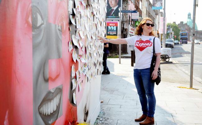 Zwolenniczka liberalizacji prawa aborcyjnego przed muralem w Dublinie przedstawiającym hinduską obywatelkę Irlandii Savitę Halappanavar, która zmarła w rezultacie komplikacji porodowych i została twarzą protestu na rzecz praw kobiet