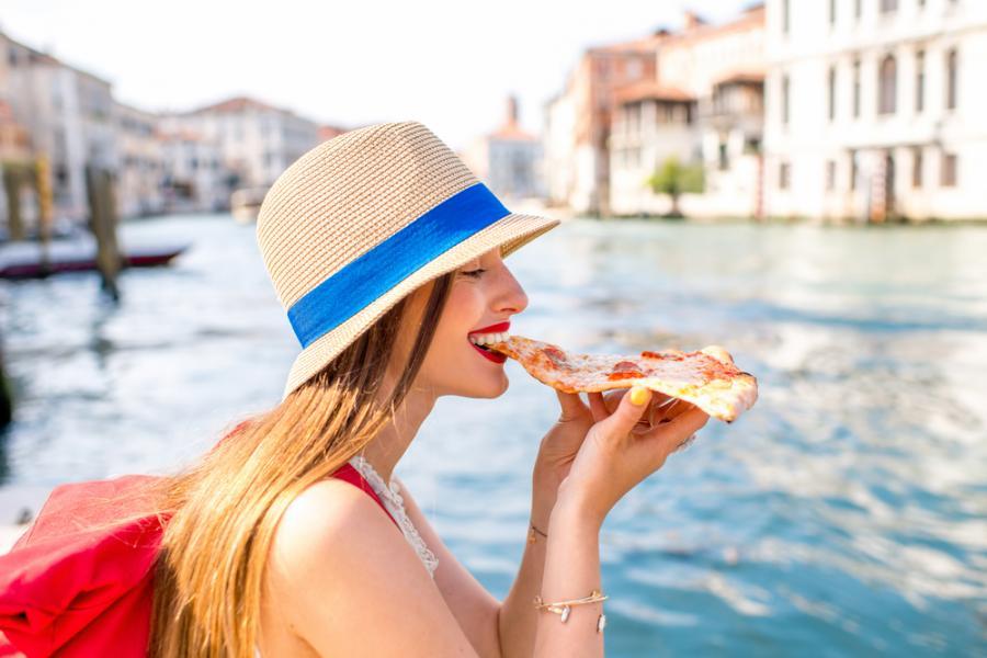 Kobieta w gondoli je pizzę