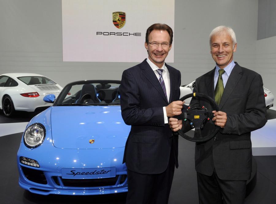 Szef Porsche Michael Macht (po lewej) przekazuje symboliczną kierownicę swojemu następcy Matthiasowi Muellerowi