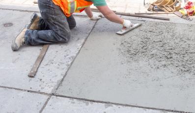 Budowlaniec wyrównujący beton na chodniku