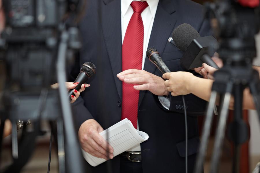 Mężczyzna przed tłumem dziennikarzy z mikrofonami