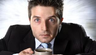 Mężczyzna z przekrwionymi oczami siedzi nad kubkiem kawy
