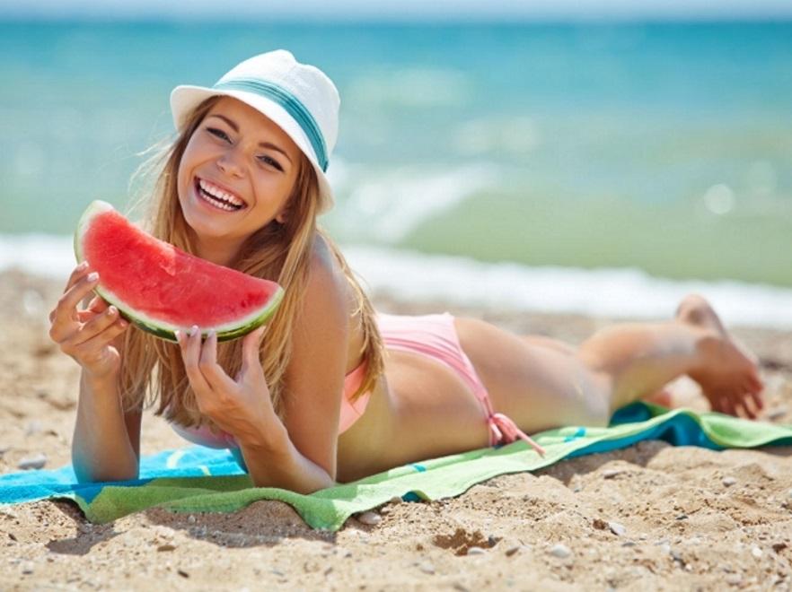 Kobieta jedząca arbuza na plaży